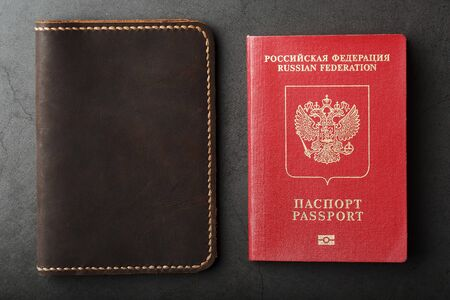 Brown leather cover with a red passport on a dark background. Russian Federation, handwork close-up. Stock Photo
