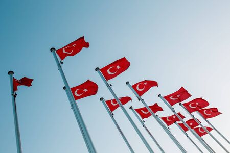 Many national Turkish Flags on the masts against the blue sky. National sign of the country Stok Fotoğraf