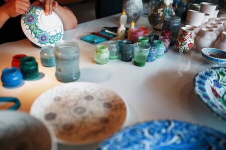 Painting porcelain plates with the hands of a professional craftsman. National Turkish craft.