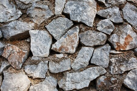 Ancient wall of gray stones, as a background, substrate. Ancient buildings, texture