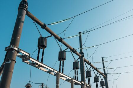 High voltage power lines with voltage against a blue sky. Live substation. Energetics Stockfoto