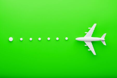White passenger plane with trajectory points as on a route map, isolated with a bright green background. Conceptual graphic element for air travel presentation. Foto de archivo