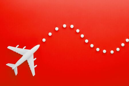White passenger plane with trajectory points, as on a route map, isolated with a red background.