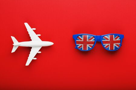 A white passenger plane flies in Sunglasses with the flag of the United Kingdom, on a red background. The concept of travel in England. Free space. illustrations for presentations, invitations.