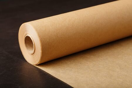 Eine Rolle ungefaltetes braunes Pergamentpapier zum Backen von Speisen auf dunklem Hintergrund, Draufsicht. Papyrus