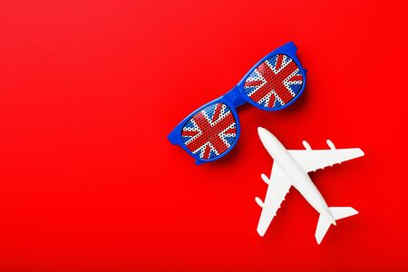 A white passenger plane flies in Sunglasses with the flag of the United Kingdom, on a red background. The concept of travel in England. Free space. illustrations for presentations, invitations. close-up