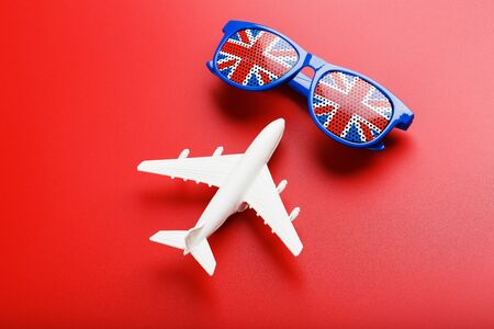 A white passenger plane flies in Sunglasses with the flag of the United Kingdom, on a red background. The concept of travel in England. Free space. illustrations for presentations, invitations. The concept of a portrait, close-up