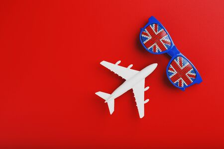 White airplane and sunglasses with the flag of the United Kingdom on a red background. Travel to England. Free space. Soft contrast Stock Photo