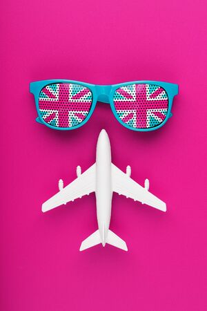 Turquoise sunglasses with United Kingdom flag in lenses on crazy pink background with white airplane. Travelling to England. Freedom and equality
