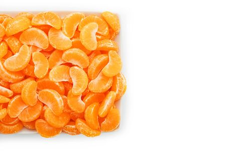 Slices of juicy tangerines in a white plate on a white background. Useful fruit. Islost