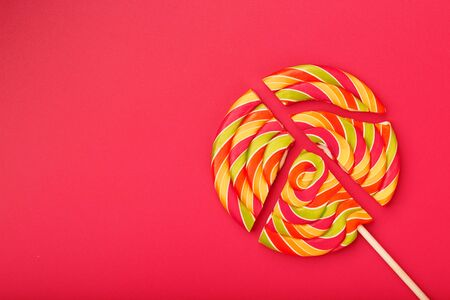 Lollipop broken into pieces on pink, red, blue background, top view with copy space. Sweet candy concept.