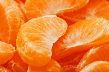 Slices of juicy tangerines close up as background texture.