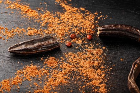 Carob carob fruit with powder on black background. Blast the Sweet powder from the pulp of the pods. Substitute cocoa and sugar, chocolate patients with diabetes and overweight people.