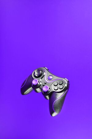 Game controller gamepad with pink buttons on lilac background. Device to control and control the game. Video games on PC, console, smartphone.