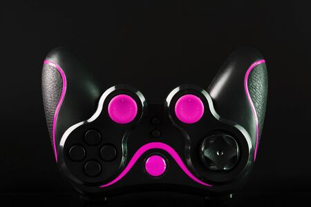 Black game controller gamepad with pink buttons on black background upside down close up . Device to control and control the game. Video games on PC, console, smartphone.