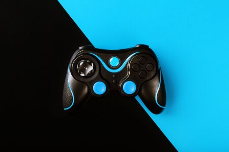 Black gamepad on black and blue background, by . Game concept. Device to control and control the game. Video games on PC, console, smartphone.