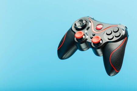 Black gamepad on a black red background, . Gaming concept. Device to control and control the game. Video games on PC, console, smartphone.