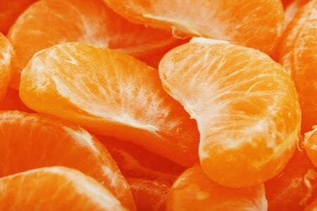 Slices of juicy tangerines close up as background texture. Useful fruit on the whole screen. Macro