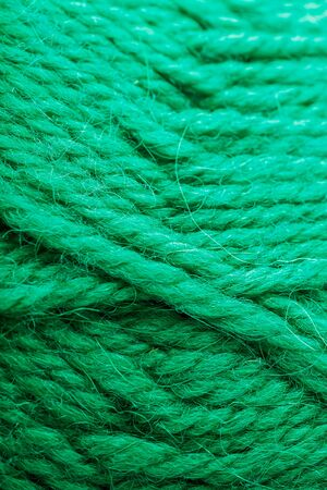 Wool yarn close up colorful aquamarine threads for needlework in macro. Background texture fabric for knitting needle. Full screen wool yarn.