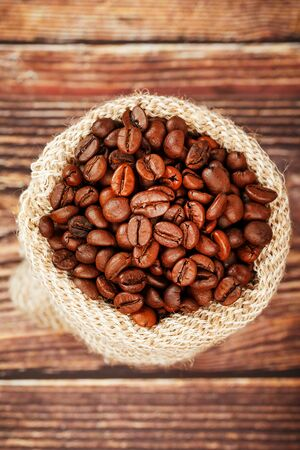 Freshly roasted aromatic coffee in a burlap bag on a wooden background. Coffee beans, for drinks