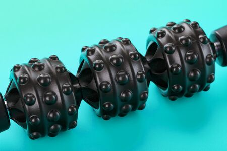 Black bumpy foam body massage roller on a blue background. For the mechanical and reflex effects on tissues and organs.