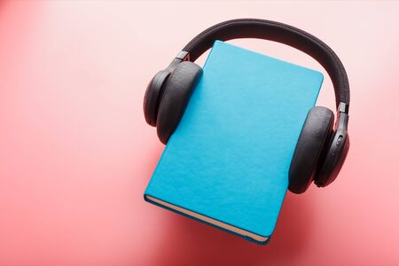 Headphones are worn on a book in a blue hardcover on a pink background, top view. The concept of Audiobook and Distance education, e-learning. Copy space