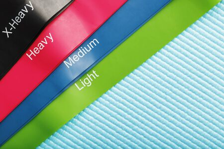 Fitness elastic bands of different colors and loads for sports on a blue background. Fitness trend