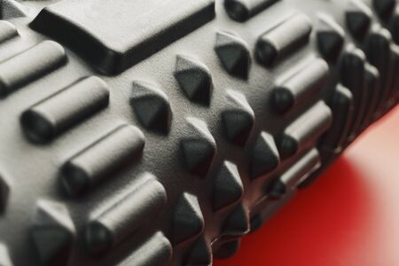Black lumpy foam massage roller on red background. For the mechanical and reflex effects on tissues and organs. Close-up, texture, element in macro Imagens