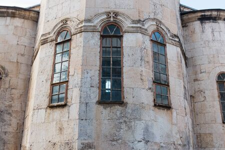 Narrow Vertical blue Windows of the Church, the castle with a wall of gray old brick. Element of historical architecture