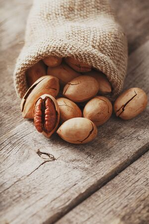 Pecans are spilled out of a burlap bag onto a wooden table in close-up. Soft contrast