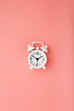 White retro alarm clock on pink background. Concept of time with free space for text. Minimalistic style, topview. 13-50 Foto de archivo - 137895775