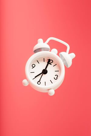 White retro style alarm clock in levitation isolated on pink background. Arrows on the time 7: 00. Minimalistic creative modern still life photography concept Foto de archivo - 137896372