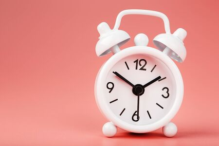 White retro alarm clock on pink background. Concept of time with free space for text. Minimalistic style, close-up.