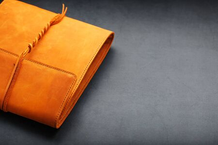 The album cover is made of brown genuine leather, handmade on a black background. Elements of a leather product close-up. Kraft
