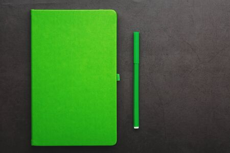 Green Notepad with a felt-tip pen on a black background, top view. Free space. 版權商用圖片