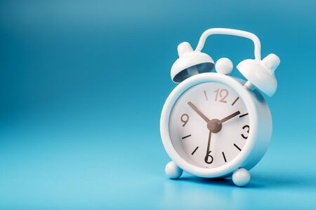 Alarm clock white on a blue background 13-50. Concept of time with free space for text. Minimal style