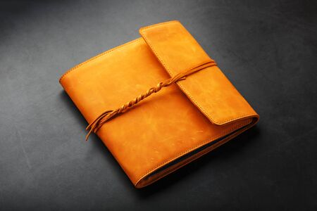 The album cover is made of brown genuine leather, handmade on a black background. Elements of a leather product close-up. 版權商用圖片