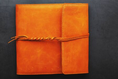 The album cover is made of brown genuine leather, handmade on a black background. Elements of a leather product close-up