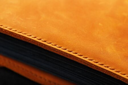 The leather cover of the album is made of brown handmade genuine leather on a black background. Elements of a leather product close-up. Craft, low contrast