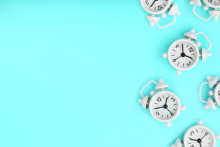 A pattern of many white classic alarm clocks in the form of a pattern on a blue background. Top view with a copy of the space, flat lay. Concept of smile time, free space