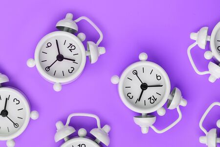 A pattern of many white classic alarm clocks in the form of a pattern on a purple background. Top view with a copy of the space, flat lay. Concept of smile time, free space 版權商用圖片