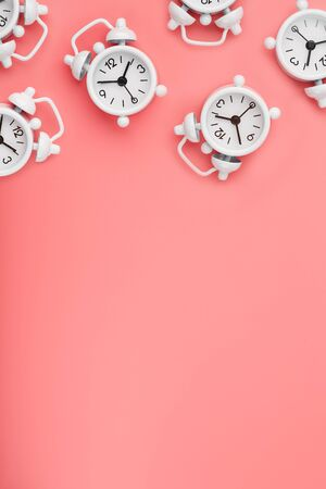 A pattern of many white classic alarm clocks in the form of a pattern on a pink background. Top view with a copy of the space, flat lay. Concept of smile time, free space