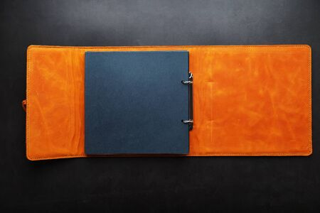Photo album with empty space for photos, white frames on black paper. Album with empty space for photos the album cover is made of brown handmade genuine leather on a black background. 版權商用圖片