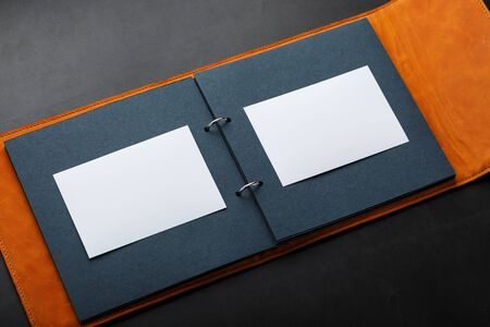 Album with empty space for photos, free space on photo paper with dark pages. The album cover is made of natural brown handmade leather on a black background. Concept
