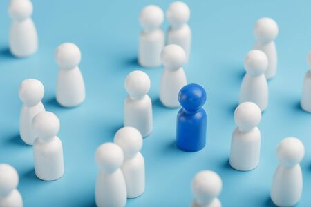 The leader of the blue color stands among the crowd, a group of white employees. The concept of leadership. Many employees are drawn to their boss. Personnel selection. How to choose a leader from a crowd of employees.