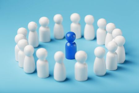 A team of white people stands around and listens to the leaders blue leader. The concept of the leader of the business team. Relationships in the team and society. 版權商用圖片