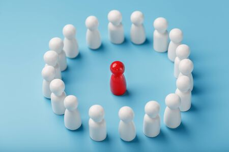 A team of white people stands around and listens to the leader of the red Leader. The concept of the leader of the business team. Relationships in the team and society.