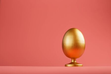 Golden egg on a pink background with a minimalistic concept. Space for text. Easter egg design templates. Stylish decor with minimal concept. Copy space, holiday flat layout of the card 版權商用圖片