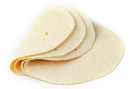 Tortilla on a white isolated background. Corn tortilla or simply tortilla is a type of thin unleavened bread made from Hominy. Bread products
