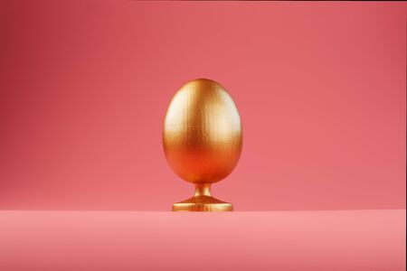 Golden egg on a pink background with a minimalistic concept. Space for text. The concept of the Easter holiday.